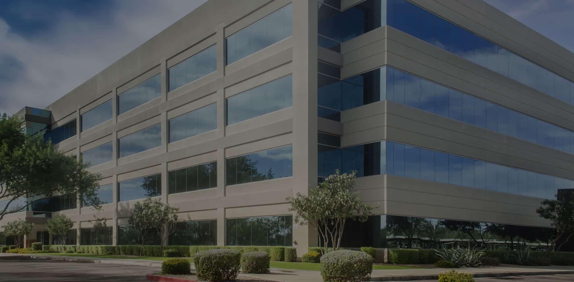 Exterior of a 4 story, big modern building and gardens