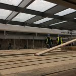 two men putting safety planks on scaffolding close to skylights