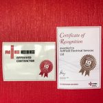 Certificate of recognition and approved contractor awarded to Airfield Electrical Services Ltd pinned up on red background