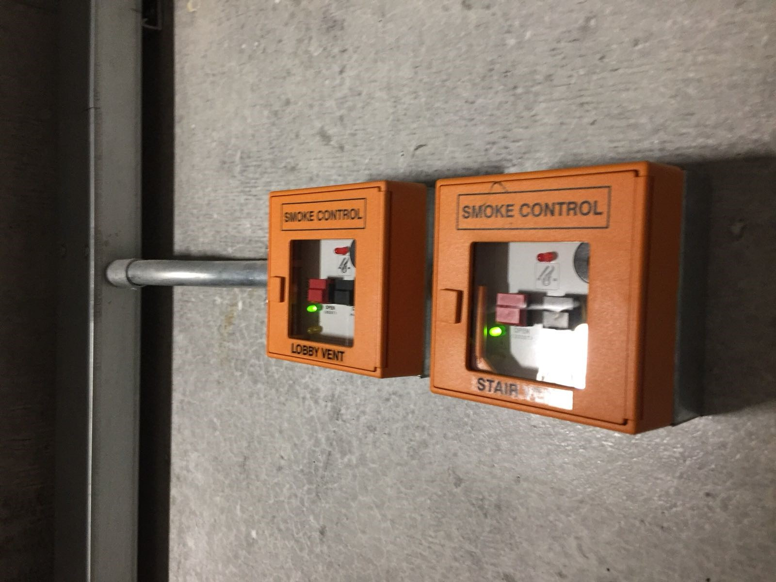 Two orange smoke control boxes located next to each other on a wall