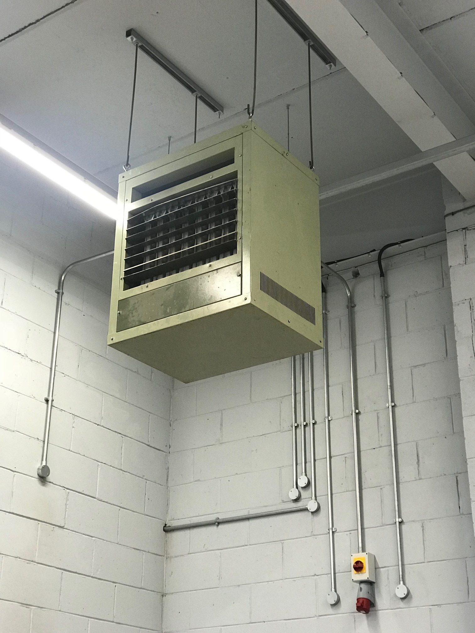 A vent hanging from the ceiling in the corner of an industrial building at boomtown